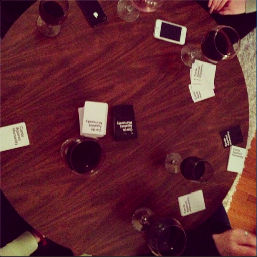 cards against humanity, iphones and drinks around the table
